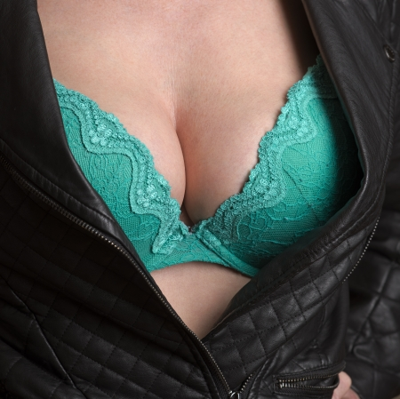 ladies bust: Woman wearing black jacket and green bra Stock Photo