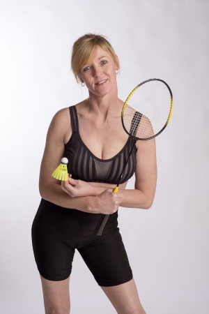 Badminton player wearing sports bra and lyrca shorts holding racquet