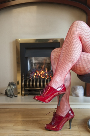 Legs in red tights by a warm fire photo