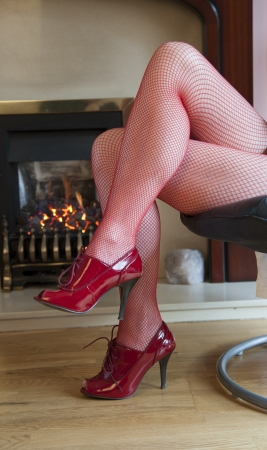 fishnets: Legs in red tights by a warm fire Stock Photo