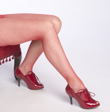 fishnet tights: Woman with long legs wearing red fishnet tights