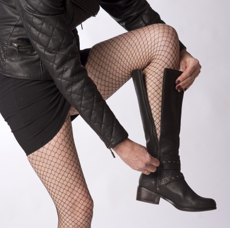 fastens: Woman wearing black fishnet tights fastening black leather boots Stock Photo