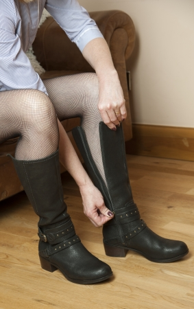fastens: Woman zipping up a pair of black leather boots