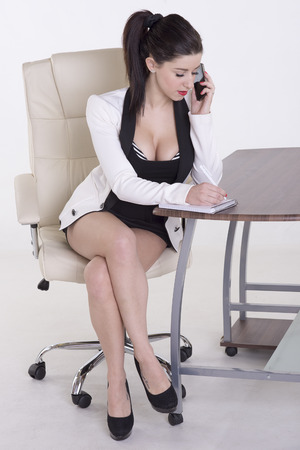 Secretary using a telephone and notebook