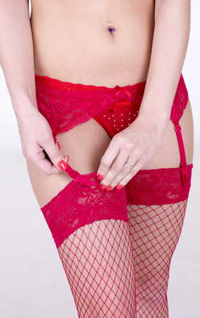 suspender: Woman fastening suspender to her stockings
