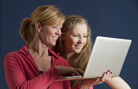 Adult and teenager looking at a laptop computer photo