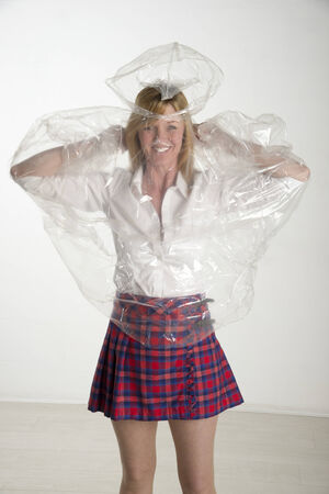 poncho: Woman putting on a plastic poncho Stock Photo
