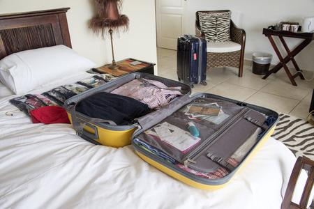 休日の服が詰め込まれている開いているスーツケース 写真素材