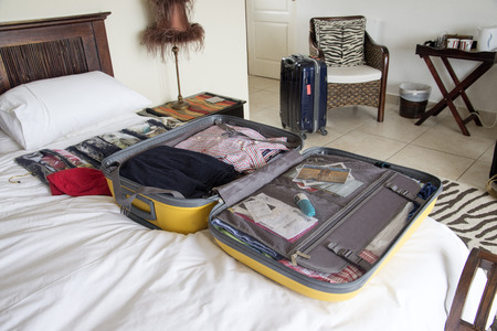 open suitcase: Open suitcase with holiday clothing being packed