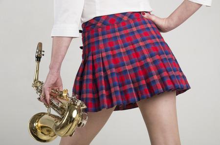 falda corta: Mujer en la falda corta que lleva un saxof�n
