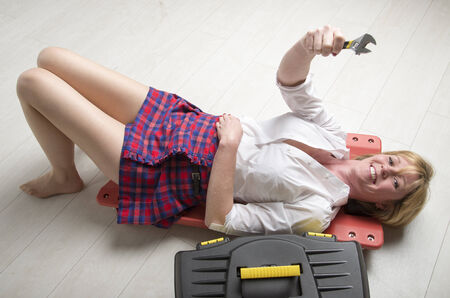 Woman using a crawler and holding a spanner Stock Photo