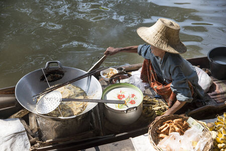Woman in straw hat selling food from her boat at a floating market Thailand