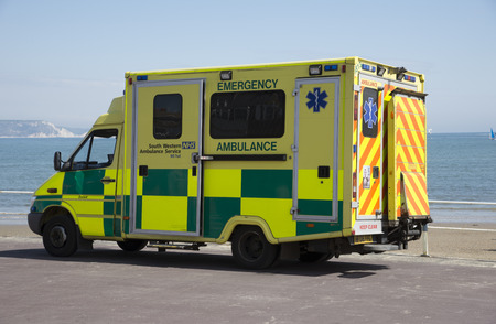 Emergency ambulance on standby at the seafront in Weymouth a seaside town in Dorset England UK