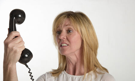 uptight: Angry woman shouting into a telephone