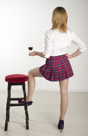 Woman with leg resting on a bar stool drinking red wine photo