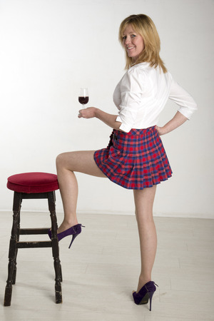 40 year old woman: Woman with leg on a bar stool drinking red wine