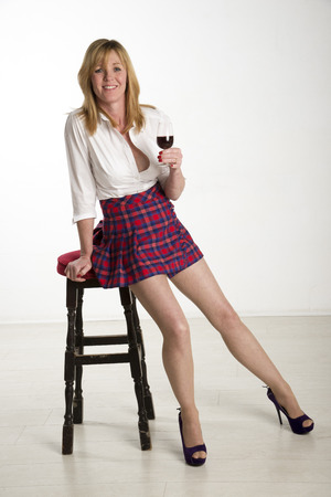 Woman leaning on a bar stool drinking red wine photo