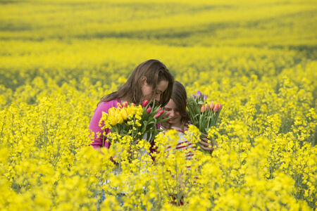 Girls with Spriing flowers in a field of rapeseed photo