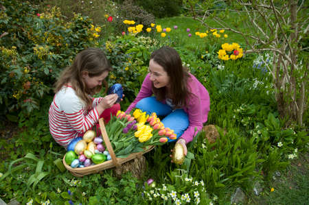 Easter egg hunt Young girls with chocolate eggs and Spring flowers photo