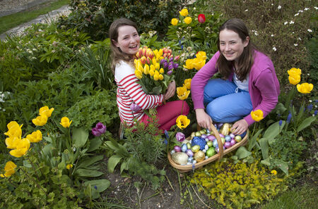 Easter egg hunt girls with their chocolate eggs and Spring flowers photo