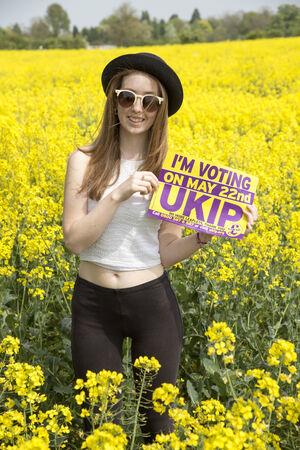 First time voter teenage girl in felt hat holding UKIP poster Imagens