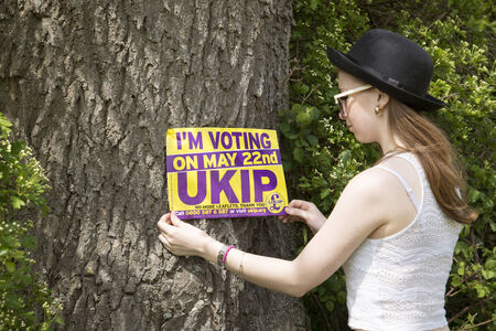 elector: First time voter teenage girl in felt hat holding UKIP poster Stock Photo
