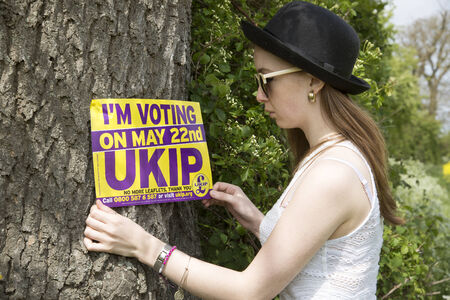 First time voter teenage girl in felt hat holding UKIP poster Stock Photo