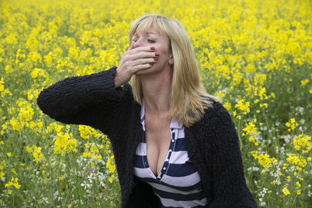 affected: Woman covering her nose and mouth in a rapeseed field Stock Photo