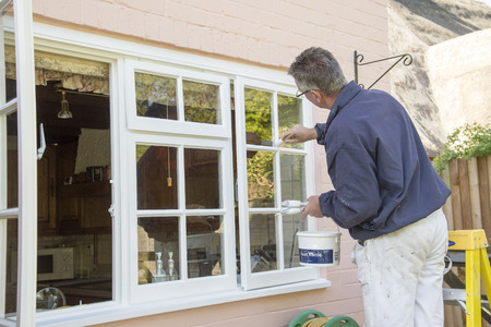 Painter painting the windows of a house