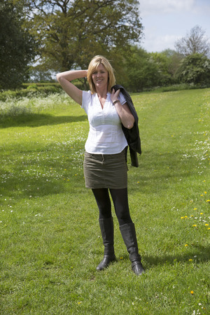 Woman standing alone in a field facing the camera photo