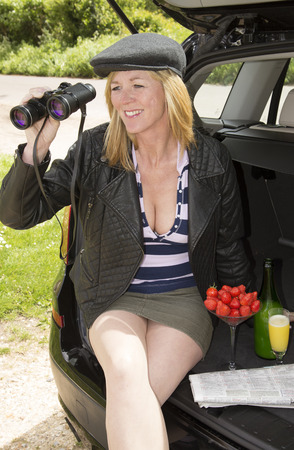 flat cap: Woman using binoculars and wearing a flat cap