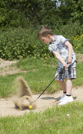 5 year old golfer playing out of a bunker photo