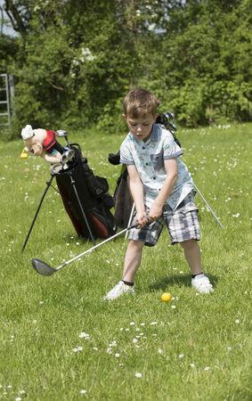 5 year old boy playing golf Foto de archivo