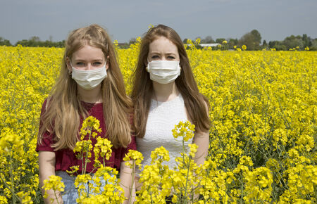 sufferer: Portrait of two teenage girls wearing a face mask allergy sufferer Stock Photo