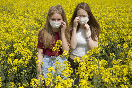hypersensitivity: Portrait of two teenage girls wearing a face mask allergy sufferer Stock Photo