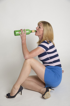 Woman drinking from a green wine bottle
