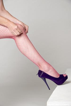 fishnet tights: Woman adjusting red fishnet tights