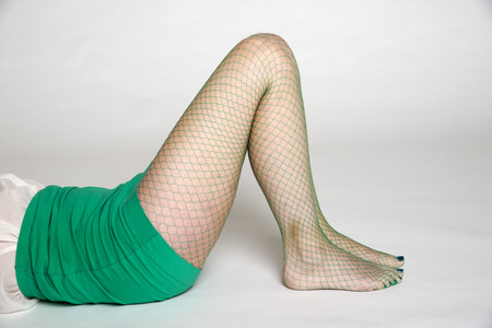 knees bent: Woman in green fishnet tights
