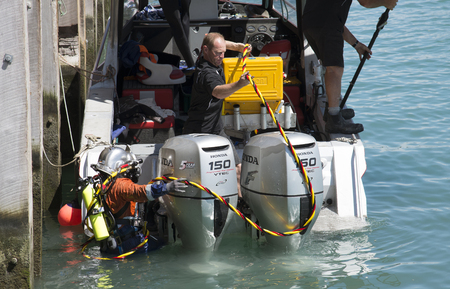 Commercial diver climbing aboard boat in Napier Port New Zealand Editoriali
