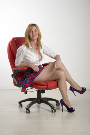 leggy: Woman sitting on a red leather chair