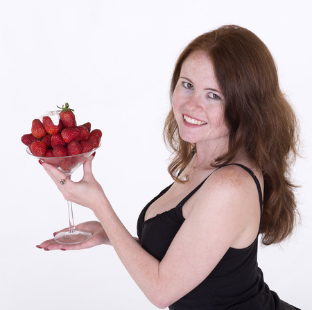 Woman eating strawberries and cream photo