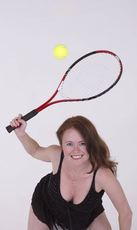 hits: Young tennis player in black dress hits the ball