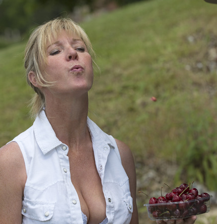 spitting: Portrait of a woman spitting out a cherry stone Stock Photo