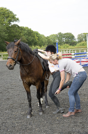 Young female rider gets help to mount her pony