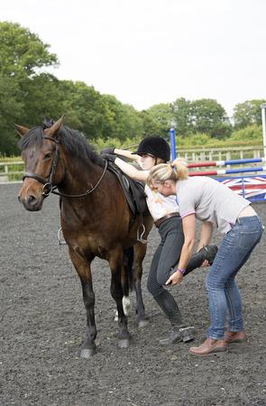 Junge weibliche Fahrer wird dabei helfen, ihr Pony zu montieren Standard-Bild - 29679766