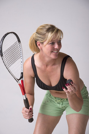 Woman in sports bra and green shorts playing squash Stock Photo