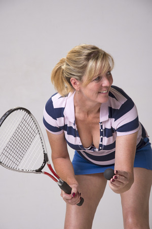 Female squash player in blue and white outfit holding ball and racquet photo