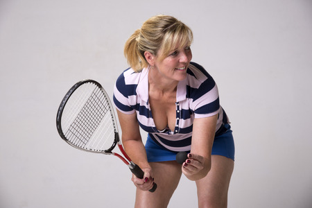 Female squash player in blue and white outfit holding ball and racquet Stock Photo