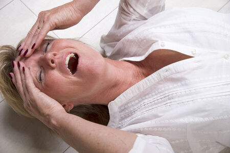 Woman laying on the floor with mouth open photo