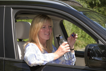 drinking and driving: Woman driver seated in car holding bottled water
